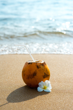 delicious cocktail in coconut on sandy beach with flower