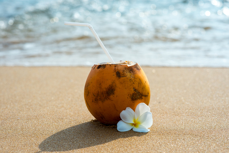 cocktail in coconut on sandy beach with flower Banco de Imagens