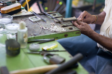 cropped shot of oriental jewelry master making rings at sri lanka manufacture Banco de Imagens