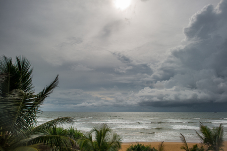 폭풍이 하늘 위에 태양이 빛나는 열 대 섬 바다 위로