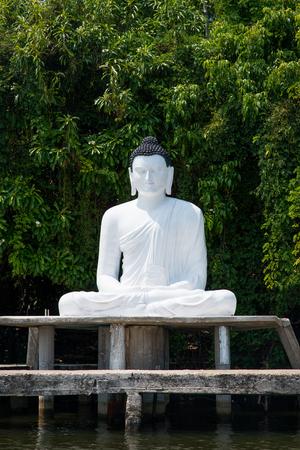 sitting buddha statue on river bank in Sri Lanka Stock Photo
