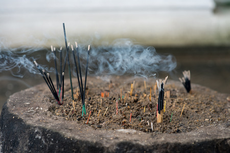 close-up shot of incense sticks burning in buddha temple