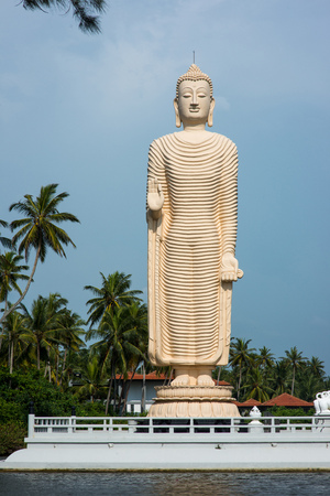 standing buddha statue on river bank in Sri Lanka