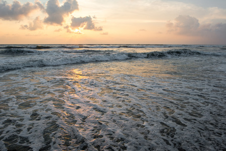 tranquil sunset over wavy sea on tropical island