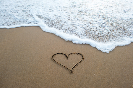 heart shape sign erasing by ocean wave on sandy beach Stock fotó