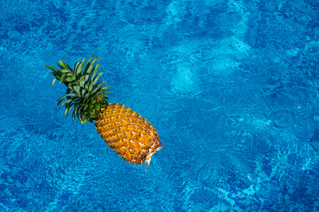 pineapple floating in blue water of swimming pool