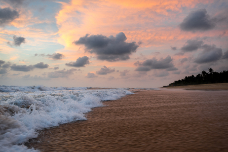 물결 모양 바다와 열 대 해변 위에 아름 다운 석양
