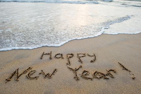happy new year sign on sandy ocean beach