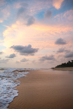 beautiful sunset over tropical beach with wavy ocean
