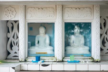 buddha statues behind glass at Sri Lanka temple