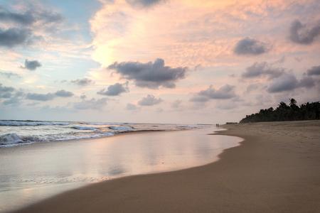 물결 모양 바다와 고요한 열 대 해변 위에 아름 다운 석양 스톡 콘텐츠