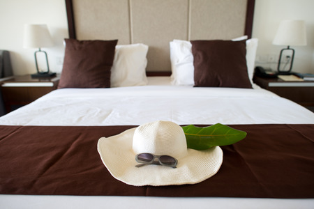 hat with sunglasses on bed in hotel room