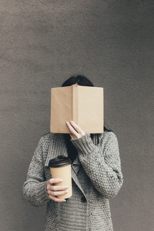 cropped view of woman in sweater holding book and coffee to go