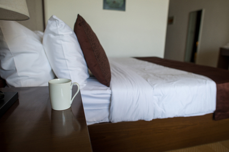 cup of coffee on nightstand in hotel room