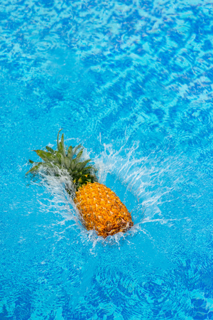 high angle view of pineapple falling in water of swimming pool
