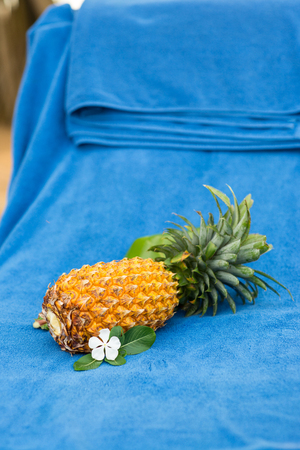 fresh pineapple with flower on blue towel