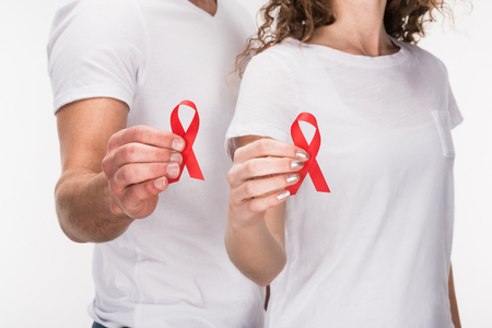 cropped view of couple holding red aids ribbons, isolated on white