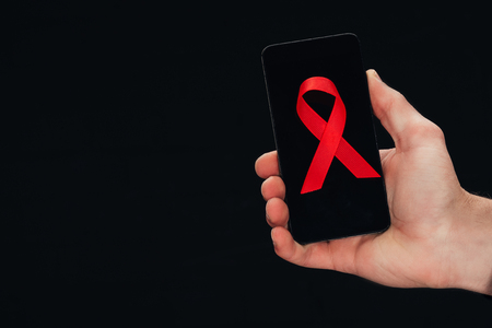 cropped view of hand with smartphone with red aids ribbon, isolated on black Stock Photo