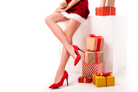 low section of sexy girl in santa costume with presents and gift boxes, isolated on white  Banque d'images