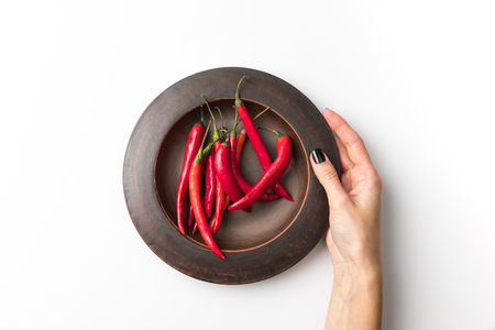 woman holding plate with chili peppers