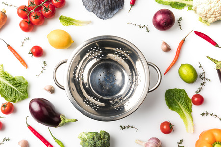 colander among uncooked vegetables