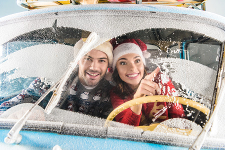 couple in santa hats driving car