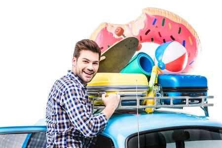 man with lugagge on car ruff