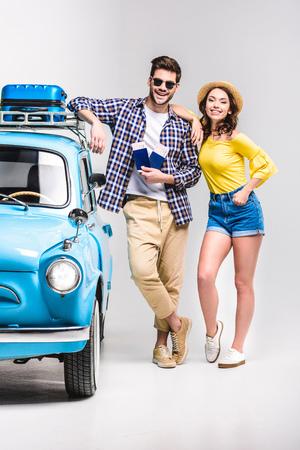 travelers standing beside car