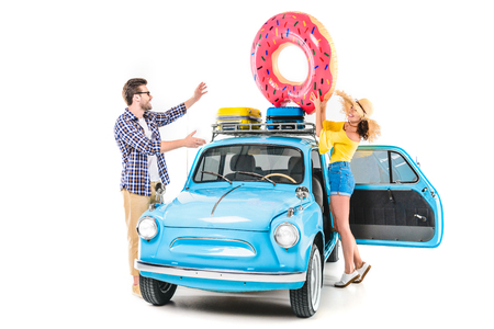 couple putting inflatable donut on car