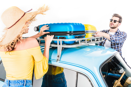 couple putting luggage on car roof Stock Photo
