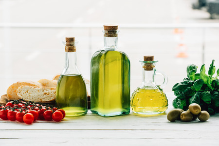 olive oil bottles with vegetables on wooden table Stock Photo