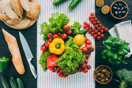 flat lay with vegetables and cooking stuff on wooden table with towel