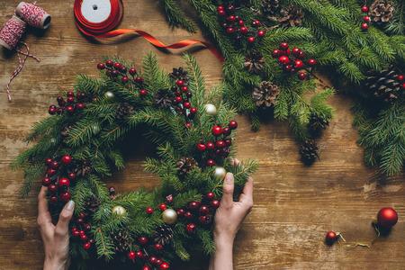 Hände halten Weihnachtskranz