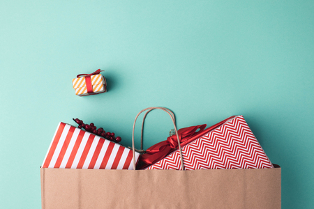 top view of wrapped presents in paper bag on blue tabletop