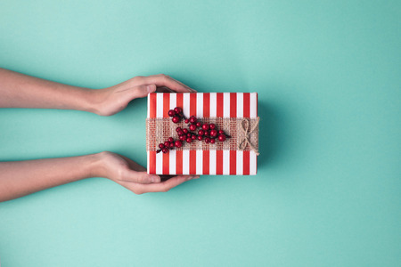 cropped shot of female hands holding wrapped christmas gift with ribbon on blue surface