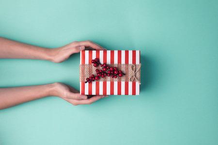 Cropped Schuss von weiblichen Händen halten verpackte Weihnachtsgeschenk mit Band auf blaue Oberfläche
