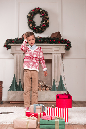 boy looking at heap of gifts