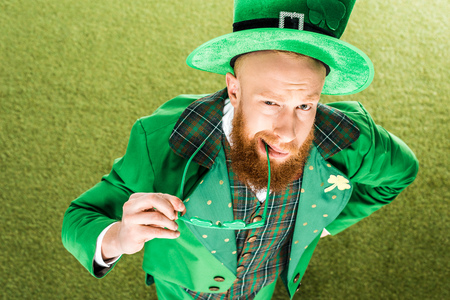 high angle view of bearded man in green costume holding clover shaped eyeglasses and looking at camera Stok Fotoğraf