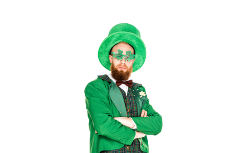bearded man in green costume and clover shaped eyeglasses standing with crossed arms