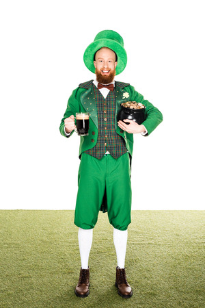 leprechaun with pot of gold and dark beer, on grass Stock Photo