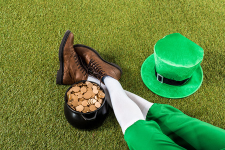 leprechaun with pot of gold and hat sitting on green grass Zdjęcie Seryjne