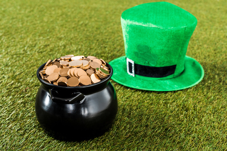 hat and pot of gold on grass for st patricks day
