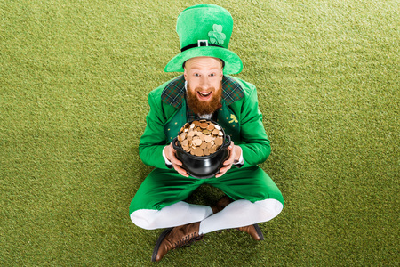 excited leprechaun with pot of gold sitting Stock Photo