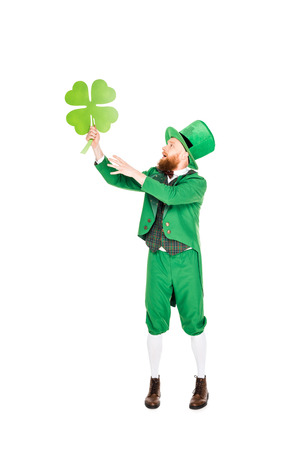 leprechaun in green suit and hat holding clover
