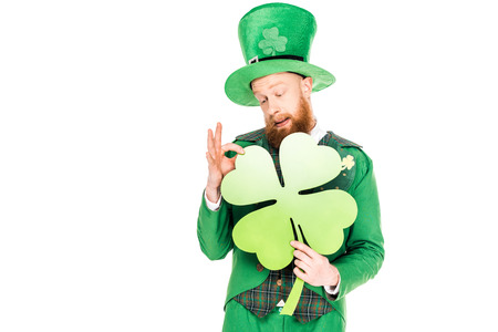 handsome leprechaun in green suit holding clover Stok Fotoğraf