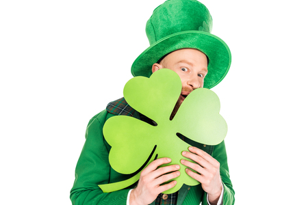 leprechaun in green suit holding clover