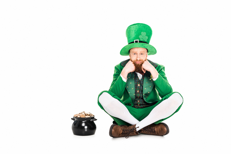 upset leprechaun in green suit sitting at pot of gold