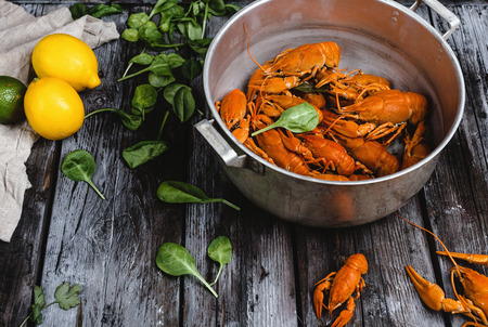 delicious lobsters in pan and herbs with citrus fruits on rustic wooden table
