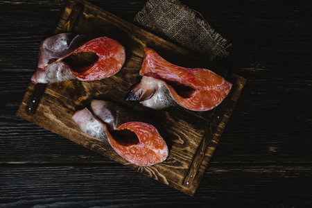 sliced salmon fish on wooden cutting board with sackcloth on rustic table Reklamní fotografie
