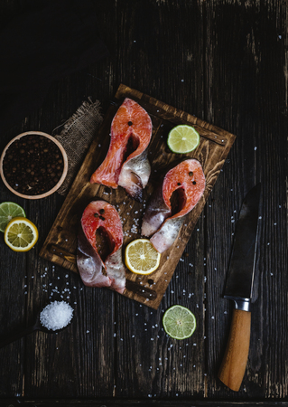 fresh sliced red fish with spices and slices of citrus fruits with knife on rustic wooden table Imagens